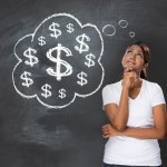Woman stands thoughfully in front of blackboard with a thougth bubble of dollar signs.