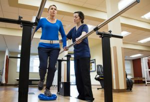 Physical therapist assistant helping a patient