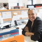 Gray haired smiling woman at desk
