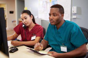 Male and female nurses at desk