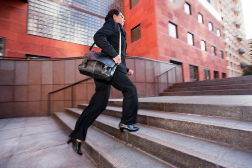 Business woman running up steps