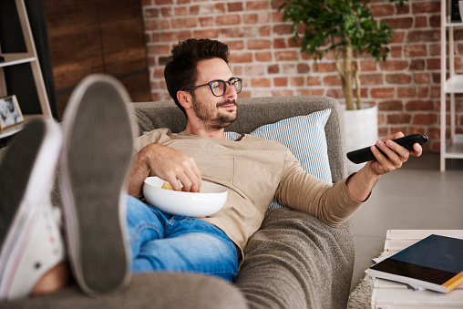man on couch watching tv eating popcorn