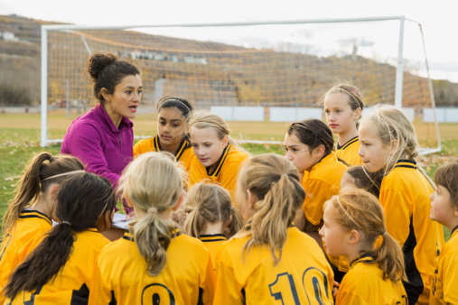 Female coach with girls soccer team