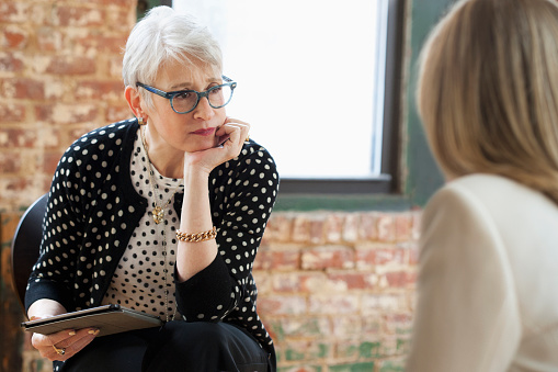 Senior woman listening to a client or patient.