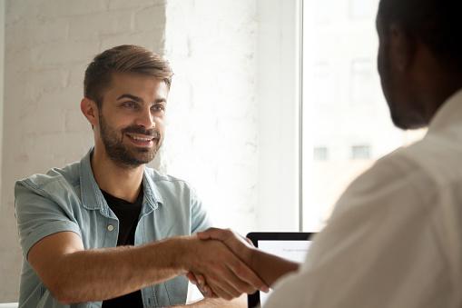 men shaking hands across a table