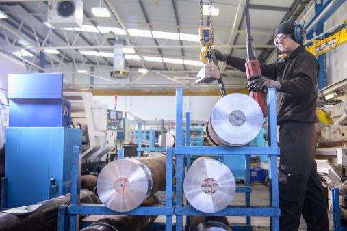 Employee using crane to lift steel in factory