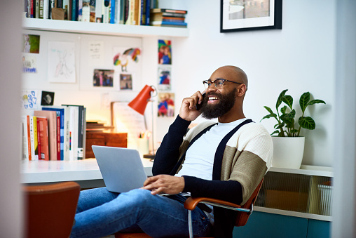 Smiling man on the phone in front of computer