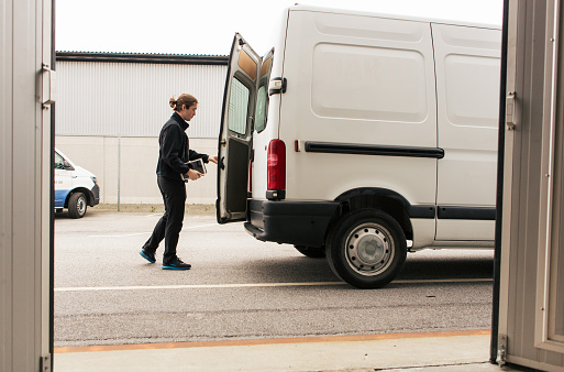 Side view of manual worker closing delivery van while standing on road