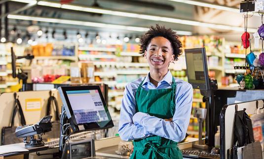 teenage boy working as supermarket cashier