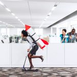 Woman speeding thru the office on the scooter with a rocket strapped to her back while her happy multiethnic co-workers are watching her succeed in the workplace