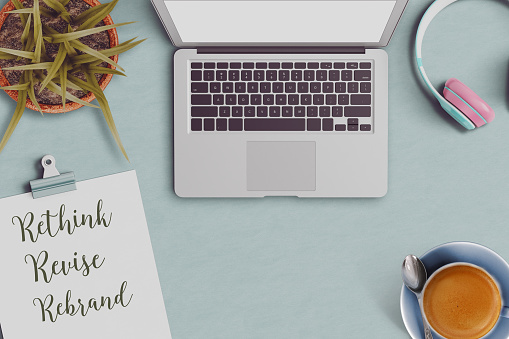 office desktop with revise rebrand and the rethink text on clipboard